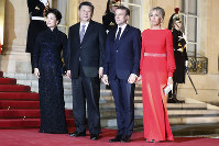 French President Emmanuel Macron, second from right, his wife Brigitte, right, welcome Chinese President Xi Jinping, second from left, and his wife Peng Liyuan, left, prior to a state dinner at the Elysee Palace, in Paris, on March 25, 2019. (AP Photo/Thibault Camus)