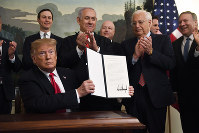 U.S. President Donald Trump holds up a signed proclamation recognizing Israel's sovereignty over the Golan Heights, as Israeli Prime Minister Benjamin Netanyahu, center, looks on in the Diplomatic Reception Room of the White House in Washington, on March 25, 2019. (AP Photo/Susan Walsh)