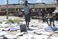 Schoolchildren pick up books that were left to dry in the sun after their school was damaged by Cyclone Idai, in Inchope, Mozambique, on March 25, 2019. (AP Photo/Tsvangirayi Mukwazhi)