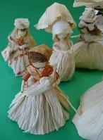 トウモロコシの皮やひげ、タマネギの皮でできた人形。手前の人形はスリングに入った赤ちゃんを抱く姿が愛らしい