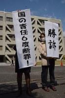 松山地裁の判決を受け、「勝訴」などと書かれた幕を掲げる支援者ら=松山市で26日、花澤葵撮影