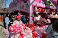 飛ぶように売れるサクラの髪飾りやアイス=北京市の玉淵潭公園で25日、浦松丈二撮影