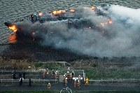 煙を上げて燃える屋形船=東京都葛飾区の荒川で2019年3月27日午後5時50分、本社ヘリから渡部直樹撮影