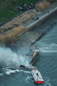 煙を上げて燃える屋形船=東京都葛飾区の荒川で2019年3月27日午後5時51分、本社ヘリから渡部直樹撮影