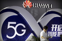 In this Sept. 26, 2018 file photo, a staff member uses a laptop at a display for 5G wireless technology from Chinese technology firm Huawei at the PT Expo in Beijing. (AP Photo/Mark Schiefelbein)