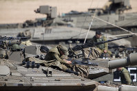 Israeli soldiers work on their tanks at a gathering area near the Israel-Gaza border, Israel, on March 26, 2019. (AP Photo/Ariel Schalit)
