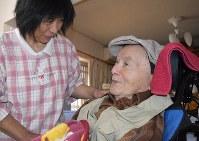 入所している高齢者施設で、宮田浩喜さん(右)に話しかけるヘルパーの園田則子さん=熊本市西区で2019年3月28日9時34分、城島勇人撮影