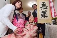宮田浩喜さん(中央)を祝福する大阪の女児焼死で再審無罪となった青木恵子さん(左)。傍らには「無罪」の旗も掲げられた=熊本市西区で2019年3月28日午後0時40分ごろ(代表撮影)