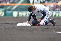 【高松商-市和歌山】初回の守備に就く際、帽子を取り三塁ベースに触れる高松商の篠原一球選手=阪神甲子園球場で2019年3月28日、山崎一輝撮影