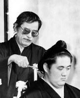 元横綱双羽黒の断髪式でハサミを入れる野坂昭如氏=東京・帝国ホテルで、1988年3月6日撮影
