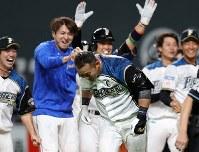 【日本ハム―オリックス】十回裏日本ハム1死満塁、サヨナラとなる左越え満塁本塁打を放ち、チームメートに出迎えられる中田(中央)=札幌ドームで2019年3月29日、貝塚太一撮影