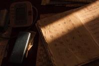 文字の練習プリントに差し込む光。写真集「失語症」より=加藤俊樹さん提供