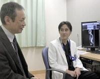 手術から7年がたち、久しぶりの再会で談笑する水田賢一さん(左)と生田真一医師=兵庫県西宮市の明和病院で