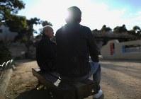 除染をさせられ逃げ込んだシェルターの運営者、平文敏さん(奥)と話すベトナム人の男性。「今も体の心配がなくならない」と話す=2019年3月24日、久保玲撮影