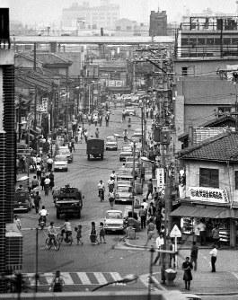 蒸し暑い夜、大勢の労働者が騒ぎ出し、投石をくりかえした暴動から1カ月が経った大阪釜ケ崎(あいりん地区)現場周辺。車や労働者が頻繁に行き交う活気のある街に戻っていた=大阪市西成区東入船町で1967(昭和42)年7月1日、乾健一撮影