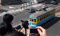 歩道橋から151号のラストランにシャッターを切る鉄道ファン=長崎市で2019年3月30日午後2時10分、今野悠貴撮影