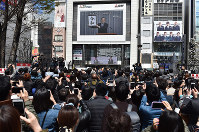 People gather to see the announcement of the new era name