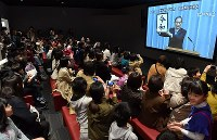 Participants enjoy a public screening event for the announcement of the new era name