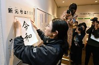 A Japan Kanji Museum & Library official displays a panel showing the new era name