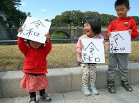 Children raise boards on which they wrote the new era name