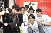 High school students take a commemorative photo while wearing T-shirts with the new era name