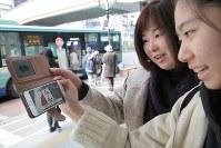 武石陽名さん(14)=右=は親子で買い物途中に新元号が気になり、菅官房長官記者会見の中継を見つめた=仙台市青葉区で2019年4月1日午前11時41分、和田大典撮影