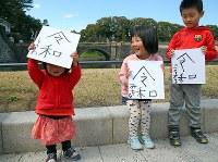 新元号の発表を受け、色紙に「令和」の文字を書いて、掲げる家族連れ=東京都千代田区で2019年4月1日午前11時49分、小川昌宏撮影