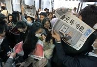新元号「令和」の発表を伝える、毎日新聞の号外配布に殺到する人たち=東京都千代田区の毎日新聞東京本社で2019年4月1日午後0時46分、手塚耕一郎撮影