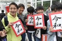 発表された新元号「令和」の字がプリントされたTシャツを手にする高校生たち=東京都渋谷区で2019年4月1日午後2時15分、藤井達也撮影