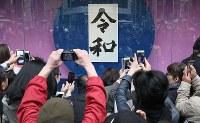 銀座「和光」前で書家の石飛博光さんが筆を執った新元号の書を写真に収める人たち=東京都中央区で2019年4月1日午後0時58分、佐々木順一撮影
