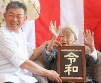 新元号「令和」を書いたチョコレートを贈呈され万歳する、116歳で世界最高齢女性の田中カ子さん(右)=福岡市東区で2019年4月1日午後2時2分、津村豊和撮影