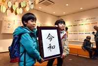 漢字ミュージアムで新元号を記入した額を手にする子どもたち=京都市東山区で2019年4月1日午後0時5分、川平愛撮影