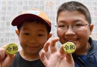 新元号「令和」の文字が入った缶バッジを手に笑顔の子どもたち=京都市東山区の漢字ミュージアムで2019年4月1日午後0時57分、川平愛撮影