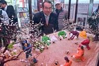 大伴旅人の邸宅で開かれた「梅花の宴」の様子を博多人形で再現した模型(手前)。中央奥は楠田大蔵・太宰府市長。新元号「令和」が太宰府に由来があり取材に応じた=福岡県太宰府市の大宰府展示館で2019年4月1日午後4時24分、野田武撮影