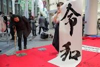 仙台市内の商店街で披露されたパフォーマンスで、聖ウルスラ学院英智高校書道部の生徒が書いた新元号「令和」=仙台市青葉区で2019年4月1日午後0時50分、和田大典撮影