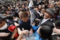 新元号「令和」を知らせる号外を手に取る人たち=東京都港区で2019年4月1日午後0時35分、尾籠章裕撮影