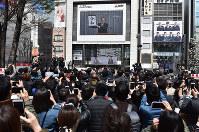 多くの人が見守る中、街頭の大型ビジョンに映し出された新元号「令和」を発表する映像=東京都新宿区で2019年4月1日午前11時41分、竹内紀臣撮影