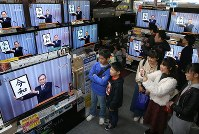 People watch a live TV program on the announcement of the new era name