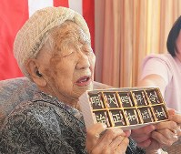 Kane Tanaka, a 116-year-old woman confirmed by Guinness World Records as the oldest person alive, is given chocolate bars that show five recent era names including