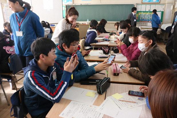 スマートフォンを使ってSNSの危険性を学ぶ児童たち。インターネットは便利だが注意点もある