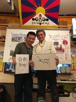This photo provided by Toru Hisatomi shows two Tibetan men living in Japan raising notes bearing the new era name