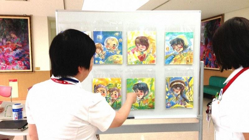村岡さんの描いた似顔絵を見る看護師たち=村岡ケンイチさん提供