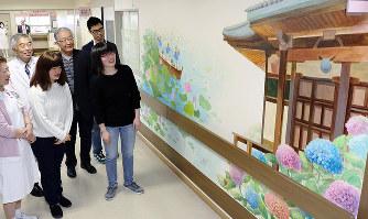 奈良県大和高田市内の季節ごとの行事や風景を描いた壁画を説明する奈良芸術短大の学生ら=同市礒野北町の市立病院で