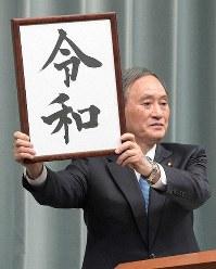 Chief Cabinet Secretary Yoshihide Suga raises a board bearing the new era name