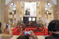 People take photos of a state carriage, similar to the one that was used for Emperor Akihito and Empress Michiko's wedding parade, on display in Tokyo's Chuo Ward, on April 3, 2019. (Mainichi/Masahiro Ogawa)