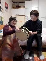 自宅で母美子さん(右)とバンドで使っている太鼓の話をする杉本明子さん=大阪市生野区で、平川義之撮影