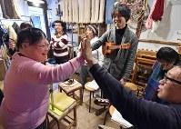 音合わせがうまくいき、笑顔でハイタッチを交わすメンバー。練習中は笑顔が絶えない=大阪市東成区で、平川義之撮影