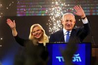 勝利宣言をしたイスラエルのネタニヤフ首相(右)。左はサラ夫人=テルアビブで10日、ロイター