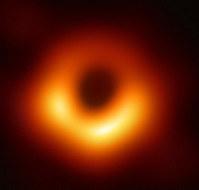 M87銀河の中心にある巨大ブラックホールの影(中央の暗い部分)をとらえた画像=国立天文台など国際研究チーム提供