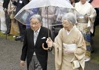 雨の中、一つの傘に入って最後の機会となる秋の園遊会に臨まれた天皇、皇后両陛下=東京都港区の赤坂御苑で2018年11月、渡部直樹撮影